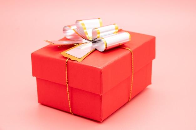 Rote geschenkbox mit weißem band und geschenken auf rosa hintergrund.