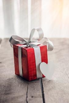 Rote geschenkbox und herz auf weißem holztisch