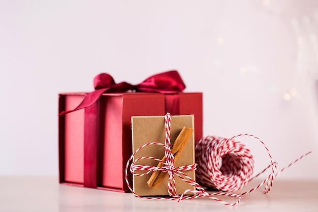Rote geschenkbox und paket mit zimtstangen und buntem seil für weihnachtsferien