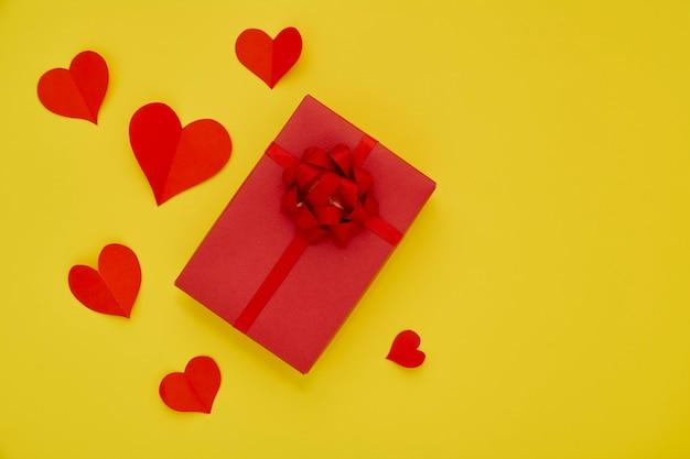 Rote geschenkbox und rote papierherzen des papiers auf gelbem hintergrund konzept-valentinstag für liebeskopienraum für text