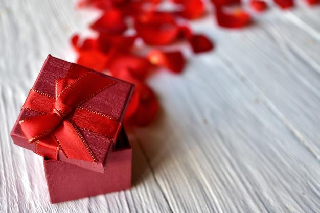 Rote geschenkbox und rote rosenblätter auf weißem holz. valentinstag konzept