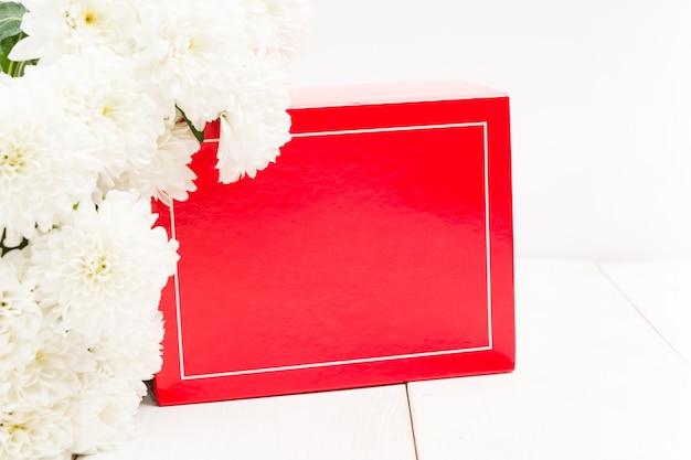 Rote geschenkbox und strauß weißer blumen