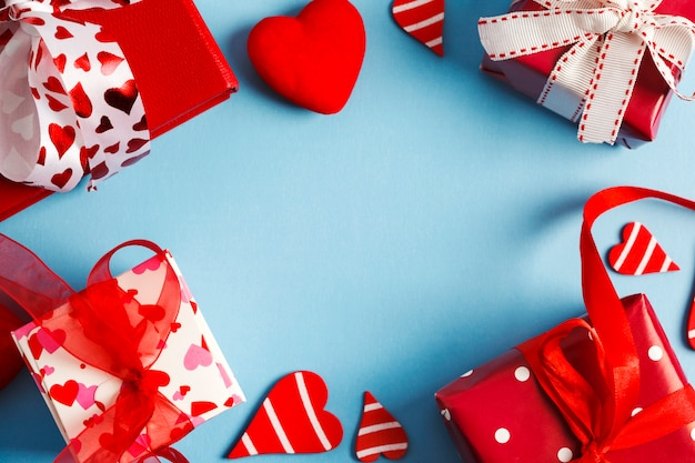 Rote geschenkboxen auf blauem hintergrund. valentinstag-konzept. draufsicht, kopie, raum