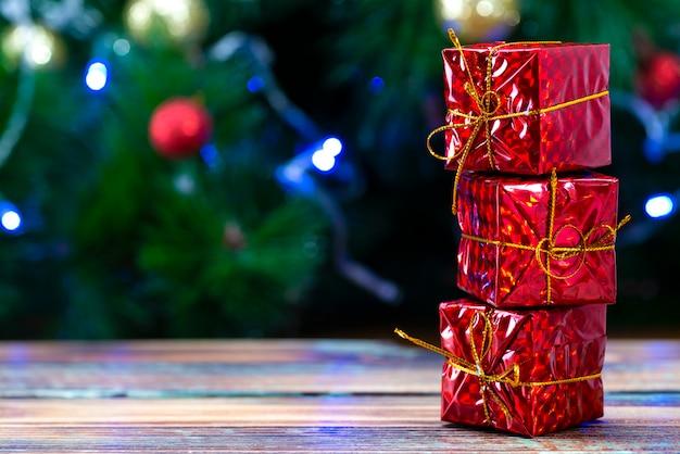 Rote geschenkboxen auf einem holztisch gegen die unschärfe von lichtern