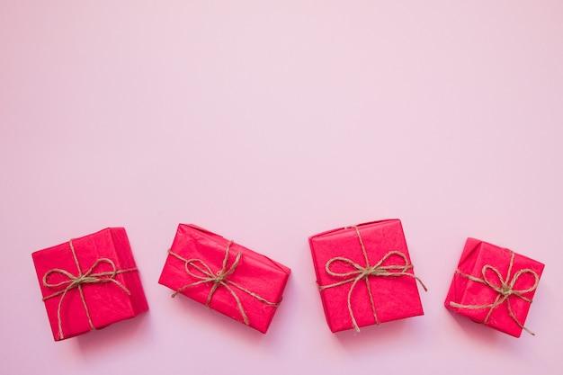 Rote geschenkboxen auf rosa hintergrund.