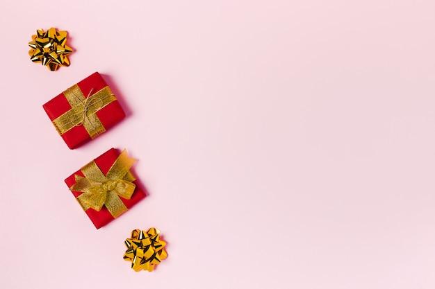 Rote geschenkboxen auf rosa tisch.