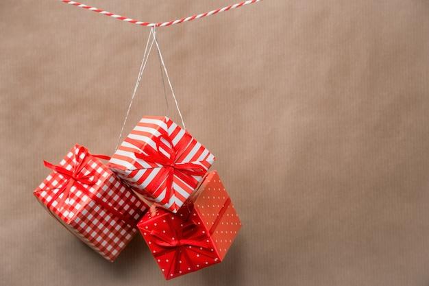 Rote geschenkboxen, die an einem band hängen. alter hintergrund des braunen papiers