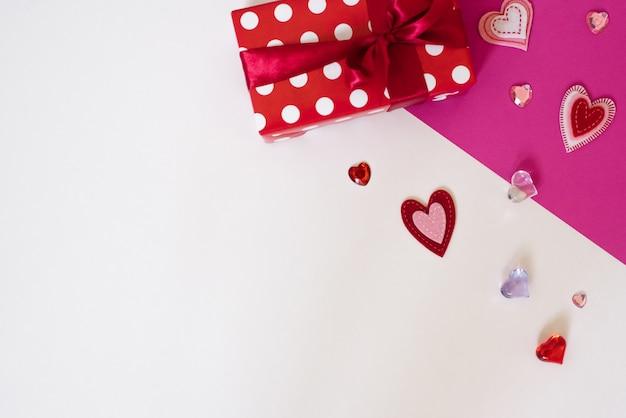 Rote geschenkboxen gucken aus einer weißen papiertüte mit herzen heraus