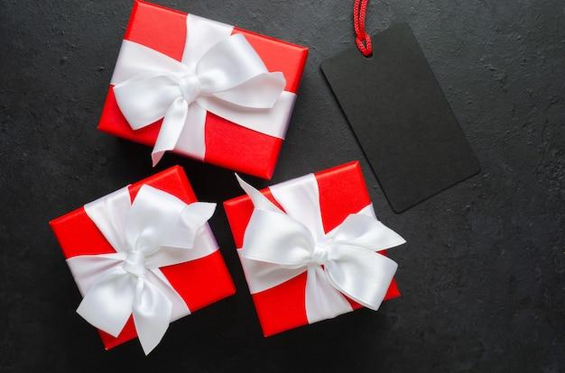 Rote geschenkboxen mit weißen bändern auf schwarzem hintergrund