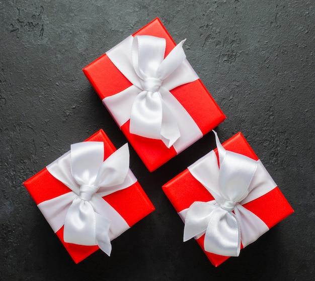 Rote geschenkboxen mit weißen bändern. schwarzer konkreter hintergrund. speicherplatz kopieren.