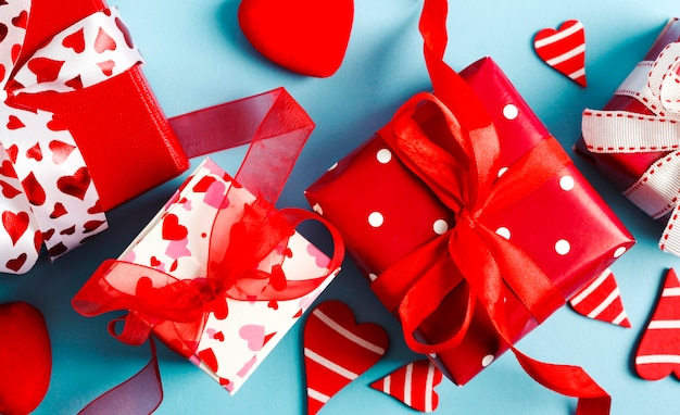 Rote geschenkboxen und rote herzen auf blauem hintergrund. valentinstagkonzept, draufsicht.