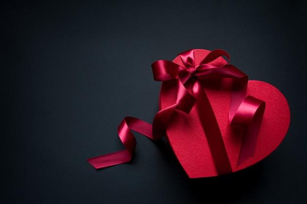 Rote geschenkboxherzform mit rotem band