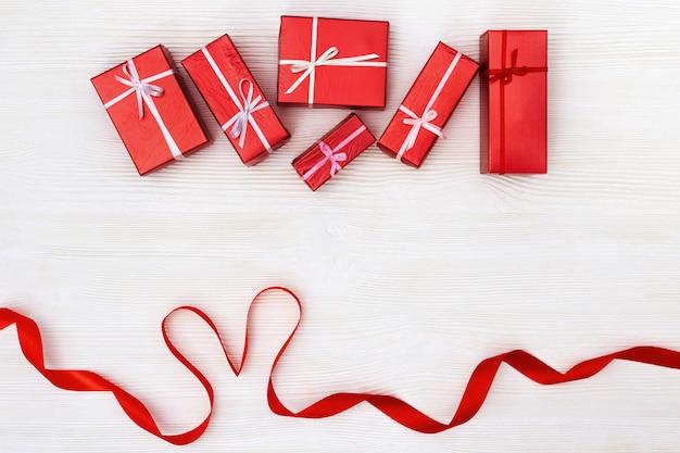 Rote geschenke auf weißem holz. präsentiert valentinstag oder frauentag. ansicht von oben. kopieren sie platz.