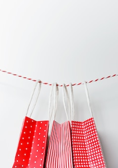Rote geschenkpaket-papiertüten, die an einem band hängen