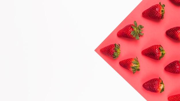 Rote geschmackvolle erdbeeren auf rosafarbenem und weißem mehrfarbigem hintergrund