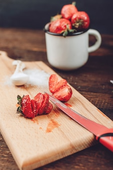 Rote geschnittene erdbeere bereitete sich für fruchttrocknergestell vor. frische erdbeeren werden gereinigt und geschnitten
