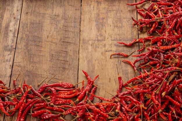 Rote getrocknete paprikas, die auf der planke gestapelt werden.