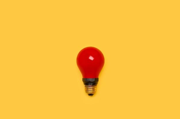Rote glühbirne auf gelbem hintergrund mit kopierraum