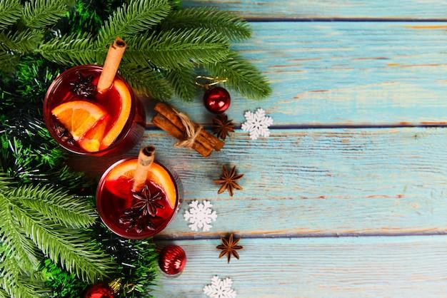 Rote glühweingläser verzierten tabelle, köstlichen feiertag des weihnachtsglühweins wie parteien mit orange zimtsternanisgewürzen für traditionelle weihnachtsgetränkwinterferien