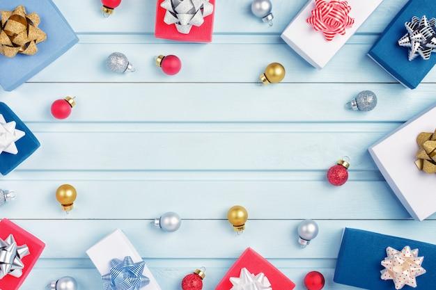 Rote, goldene und silberne weihnachtskugeln und geschenkboxen mit schleifen sind in einem kreis angeordnet