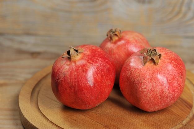 Rote granatäpfel auf einem hölzernen hintergrund