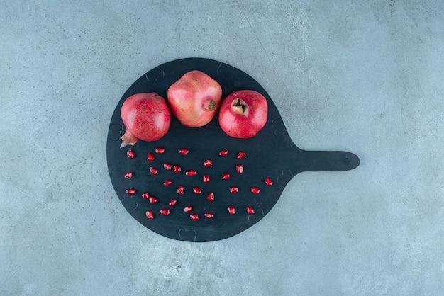 Rote granatäpfel auf einer schwarzen holzplatte.