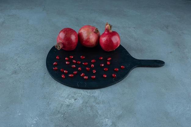 Rote granatäpfel auf einer schwarzen servierplatte isoliert.