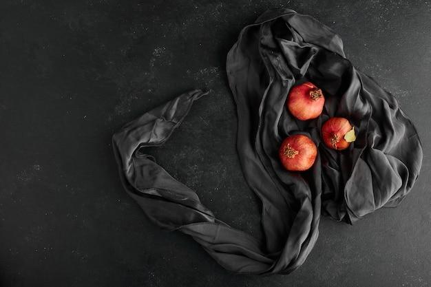Rote granatäpfel auf schwarzer tischdecke, draufsicht.