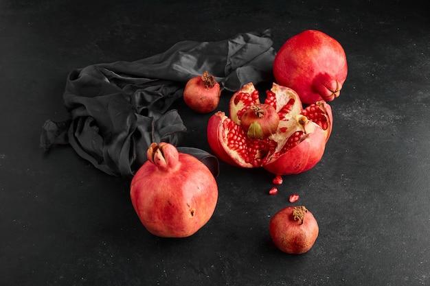 Rote granatäpfel auf schwarzer tischdecke und raum, winkelansicht.