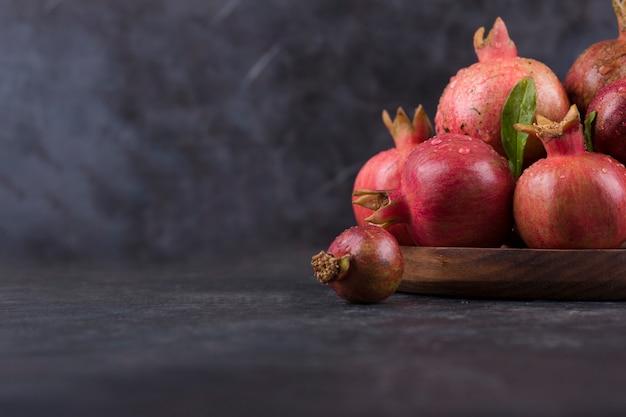 Rote granatäpfel in einer holzplatte auf marmor