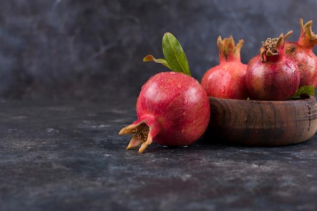 Rote granatäpfel in einer holzplatte und auf dem marmortisch
