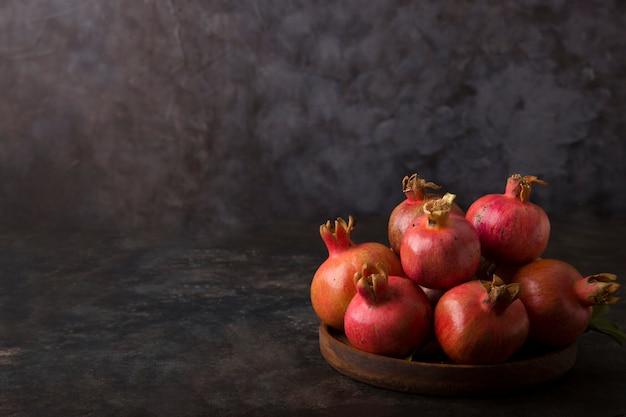 Rote granatäpfel in einer holzplatte