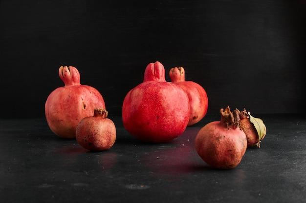 Rote granatäpfel in kleinen und großen formen auf schwarzer oberfläche.