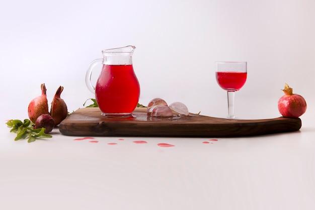 Rote granatäpfel serviert mit saft und sauce