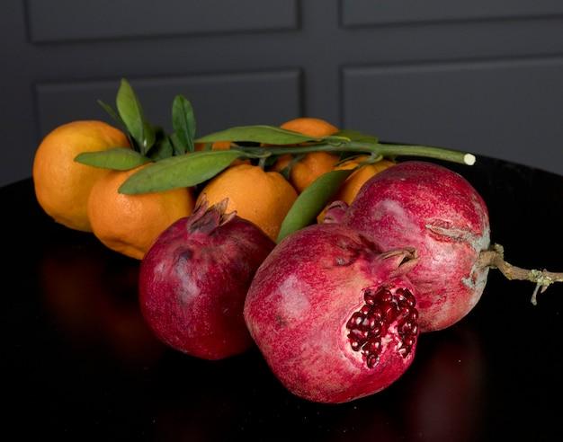 Rote granatäpfel und orangen mit grünen blättern