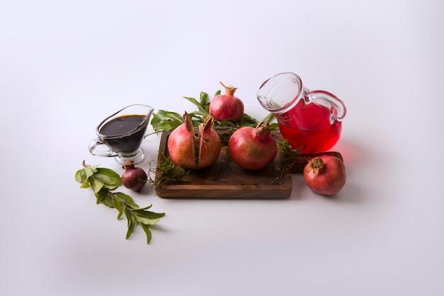 Rote granatäpfel und sauce im holzbrett