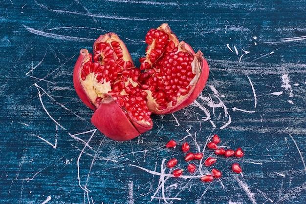 Rote granatapfelkerne auf blauem raum.