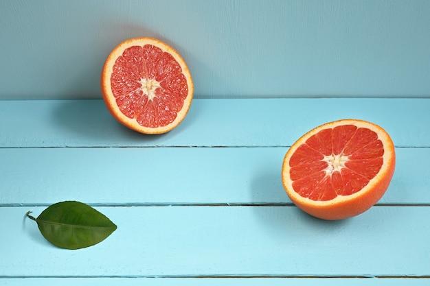 Rote grapefruit halbiert auf einem blauen rustikalen holzhintergrund.
