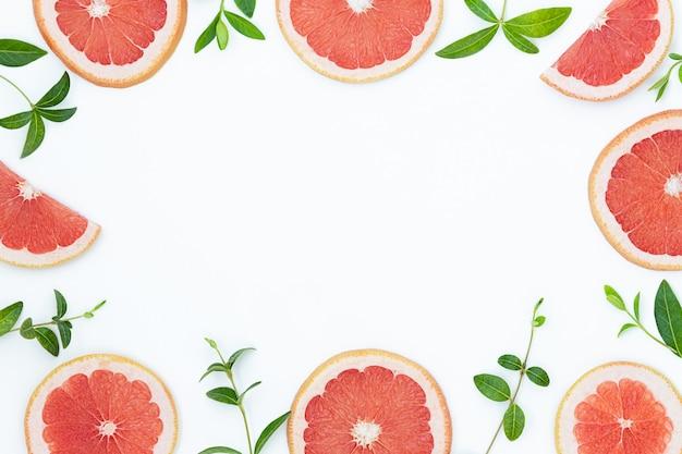Rote grapefruits und grüne blätter auf der grauen oberfläche