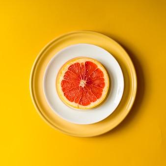 Rote grapefruitscheibe auf teller. flach liegen.