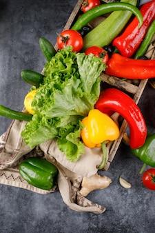 Rote, grüne, gelbe chilis mit einem haufen salat.