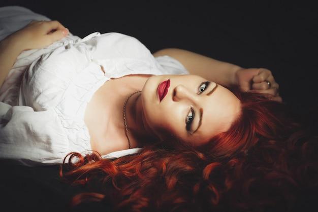 Rote haarfrau, die kamera betrachtend legt