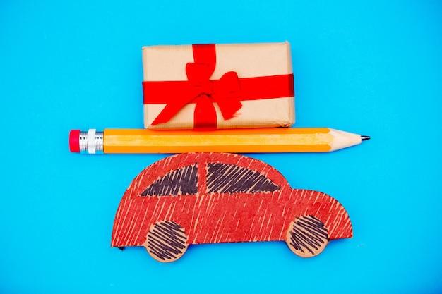 Rote handgemachte autozustellung mit weihnachtsgeschenkbox und großem bleistift