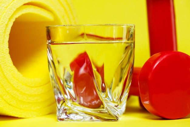 Rote hanteln, ein glas wasser, ein gelber teppich, farbiger hintergrund, sport, energy-drink, geräte für das fitnessstudio