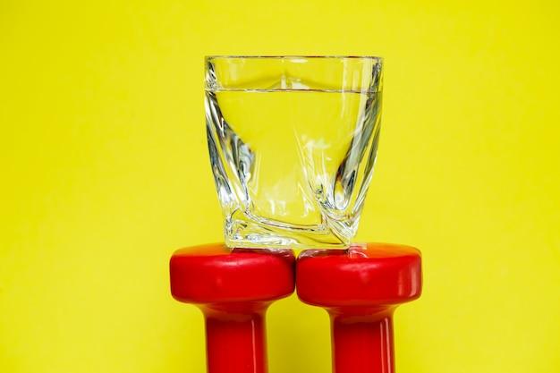 Rote hanteln, ein glas wasser, farbiger hintergrund, sport, energy drink, fitnessgeräte
