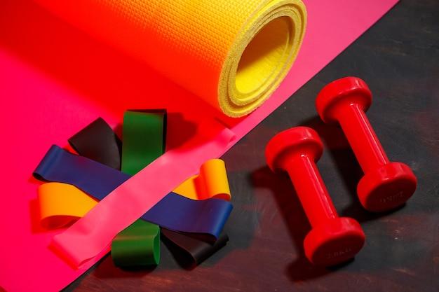 Rote hanteln, fitnessmatte und gummibänder für sport auf rosa hintergrund. gesunder lebensstil. fitnessgeräte für das krafttraining. muskelaufbau und fitnesstraining