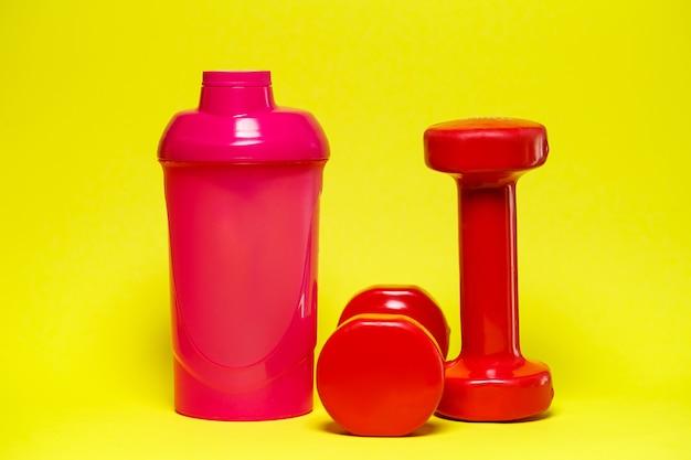 Rote hanteln, rosa shaker, farbiger hintergrund, sport, energy drink, fitnessgeräte