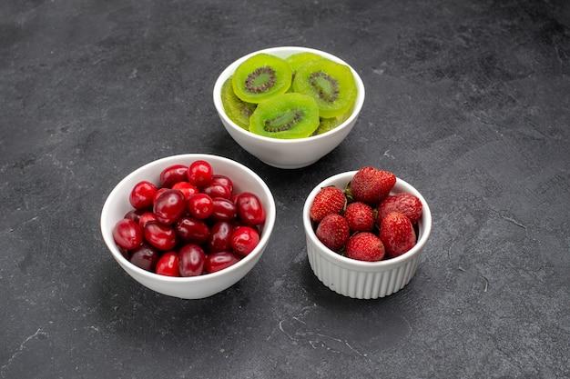 Rote hartriegel der vorderansicht mit erdbeeren und kiwi auf grauem raum