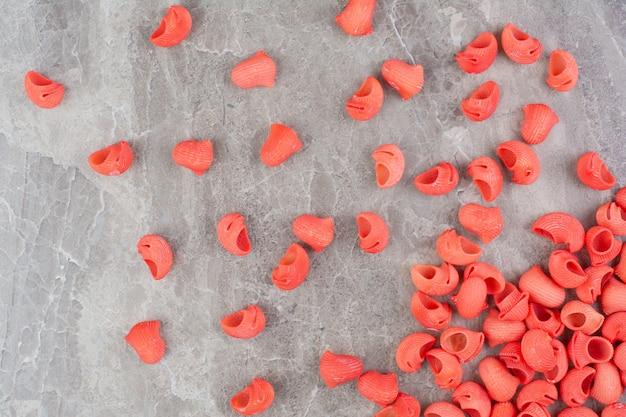 Rote hausgemachte nudeln verteilen sich auf der grauzone.
