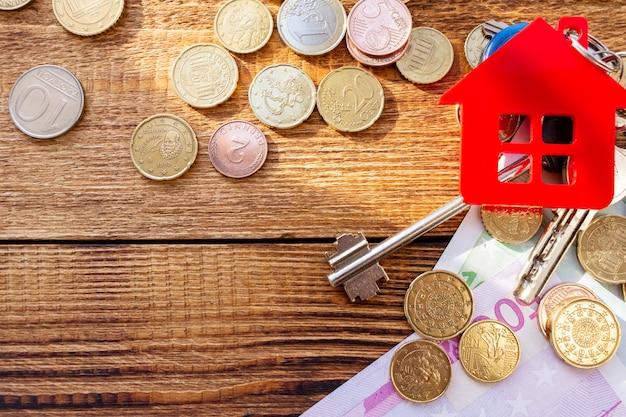 Rote hausschlüssel auf dem banknoten- und münzenhintergrund. immobilienkonzept.